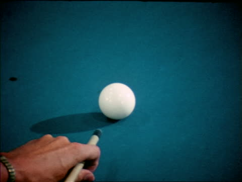 1963 zoom out from close up of man's hand shooting with cue stick to man breaking balls apart on pool table