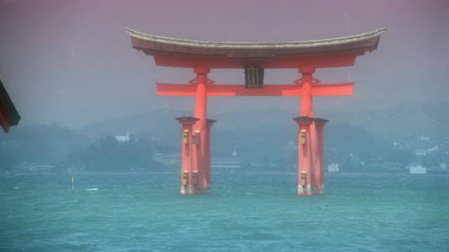 zoom out from close up of Miyajima Itsukushima Shrine torii in lake / Japan
