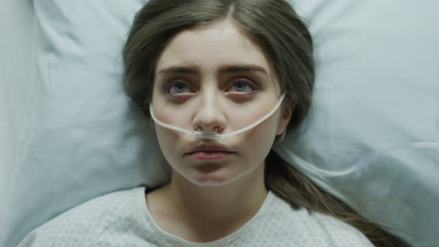 zoom out from close up of teenage girl laying in hospital bed with breathing tubes in nose / salt lake city, utah, united states - inhaling stock videos & royalty-free footage