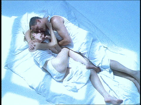 vídeos y material grabado en eventos de stock de zoom out from close up to high angle view, zoom in of couple lying in bed kissing + cuddling - pareja de mediana edad