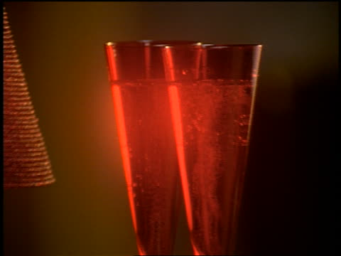 zoom out from close up two red glasses of champagne on table with rose, pearl necklace + candle / fireplace in background - valentine's day stock videos & royalty-free footage