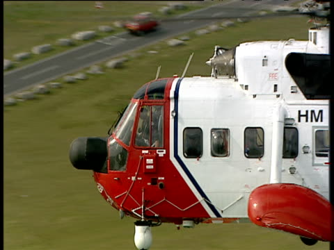 Zoom out from coastguard helicopter in flight over coastline Isle of Portland