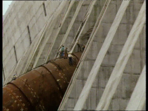 zoom out from construction workers on wall of itaipu dam brazil - brasile meridionale video stock e b–roll