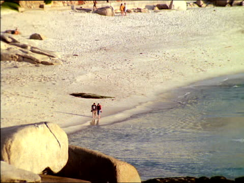 vídeos de stock, filmes e b-roll de zoom out from couple walking along beach to reveal camps bay and distant twelve apostles mountains, south africa - península