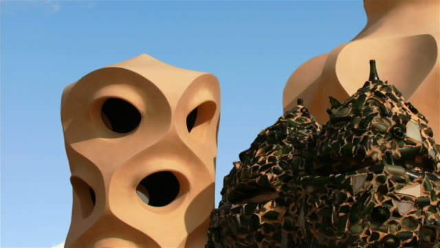 Zoom out from detail of roof of Casa Mila as clouds pass overhead in fast motion / Barcelona, Spain