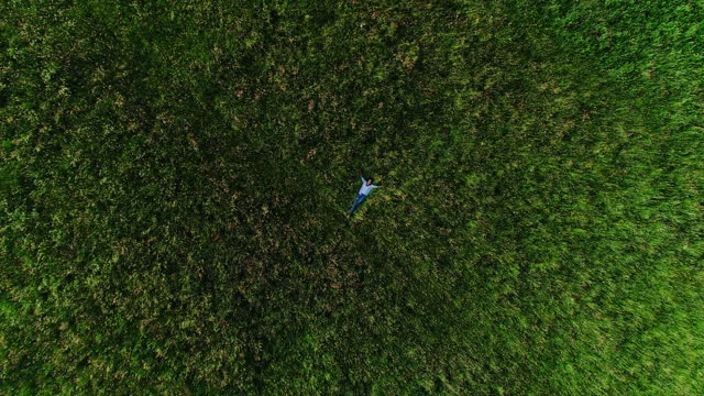 zoom out from directly above on happy young woman lying on meadow - lying on back stock videos & royalty-free footage