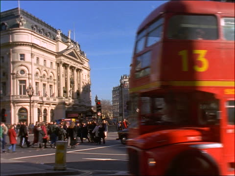 zoom out from double decker buses + crowds in Piccadilly Circus / London