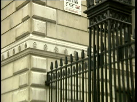 zoom out from downing street sign to workmen erecting barriers at street gates in preparation for anti capitalist demonstrations the following day; 30 apr 01 - downing street stock videos and b-roll footage