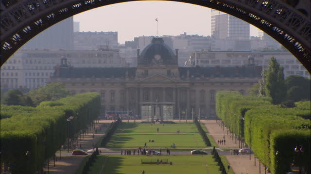 zoom out from ecole militaire on parc du champ de mars to view of park and school through base of eiffel tower / paris, france - arch stock videos & royalty-free footage