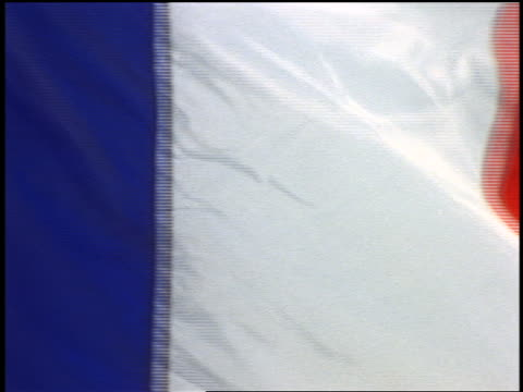 zoom out from extreme close up french flag blowing in wind / blue sky in background - french flag stock videos and b-roll footage