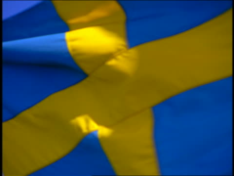 vídeos y material grabado en eventos de stock de zoom out from extreme close up of swedish flag blowing in wind / blue sky in background - suecia