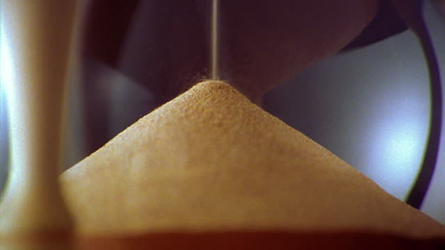 zoom out from extreme close up to close up sand falling in hourglass - hourglass stock videos & royalty-free footage