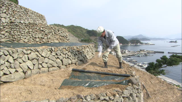 Zoom out from farmer preparing agricultural terrace and crane forward over port of Yusu and Seto Inland Sea