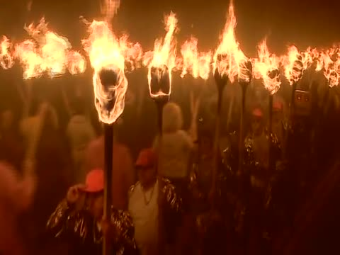 zoom out from flaming torchs to parade of guisers or costumed men for the annual up helly aa festival - galeere stock-videos und b-roll-filmmaterial