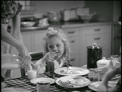 B/W 1944 zoom out from girl drinking milk to family eating breakfast in kitchen / father leaving for work