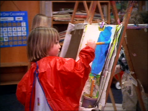 zoom out from girl wearing smock painting picture at easel with blue paint to other children painting - easel stock videos and b-roll footage