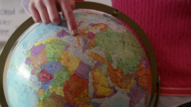 stockvideo's en b-roll-footage met zoom out from globe of planet earth / girl pointing at italy on globe while giving report in front of class / gorham, maine - bureauglobe