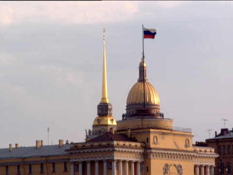 zoom out from gold dome russian flag and gold spire on ornate pillared building across harbour st petersburg - spire stock videos & royalty-free footage