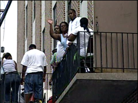 zoom out from group of people standing on fire escape above deep flood waters caused by hurricane katrina new orleans; 4 sep 05 - hurricane katrina stock videos and b-roll footage