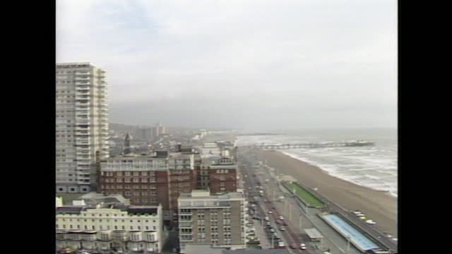 zoom out from high-rise buildings to wide shot general view of brighton seafront on an overcast day; 1986. - overcast stock videos & royalty-free footage