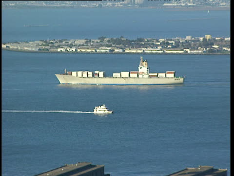 zoom out from large commercial tanker and small yacht to bay docks skyline and houses san francisco - bay of water stock videos & royalty-free footage