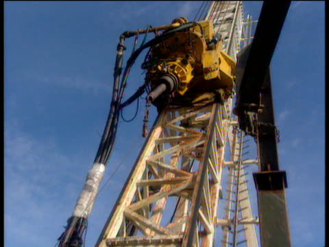 zoom out from large drill on crane moving down towards industrial workers - large stock videos & royalty-free footage