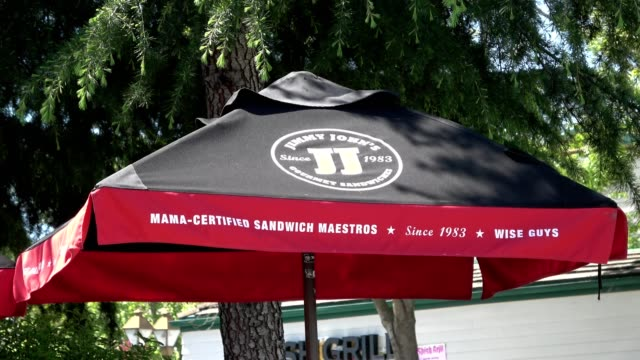 zoom out from logo of jimmy john's fast casual sandwich shop on umbrella in wooded setting outside the chain's san ramon, california location, april... - zoom in点の映像素材/bロール