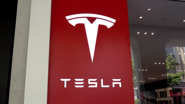 zoom out from logo on facade of tesla motors store in the silicon valley san jose california june 7 2018 - ロゴマーク点の映像素材/bロール