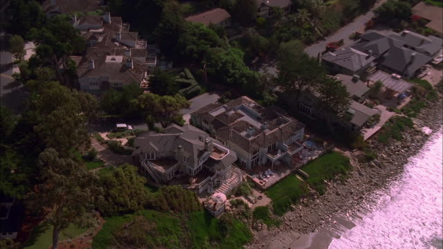 vídeos de stock, filmes e b-roll de zoom out from luxury beach side home on the malibu coast. available in hd. - hill