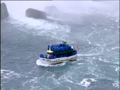 Zoom out from Maid of the Mist tourist boat to vast Niagara Falls
