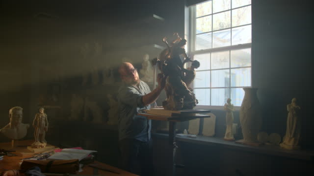Zoom out from man in studio sculpting statue in natural light from window / American Fork, Utah, United States