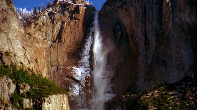 zoom out from medium shot to wide shot long shot upper yosemite falls over cliff with mist / yosemite national park, ca - upper yosemite falls stock videos & royalty-free footage