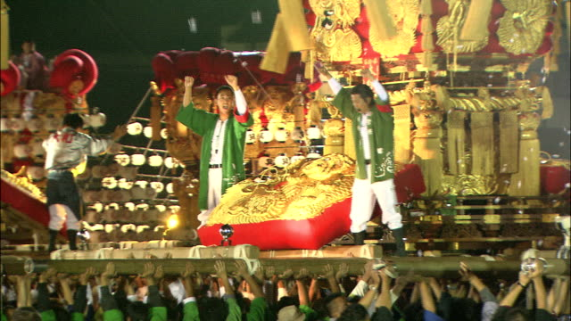Zoom out from men dancing on decorated float to crowd at festival, Japan