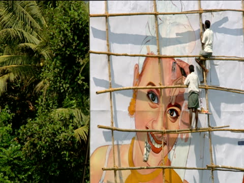 zoom out from men on wooden scaffolding painting large poster onto billboard kochi india - poster stock videos & royalty-free footage