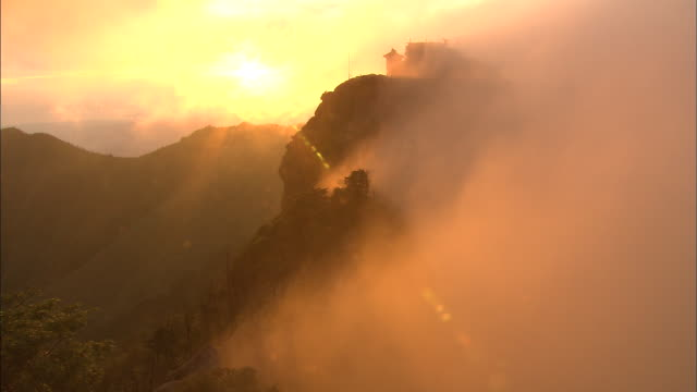 Zoom out from mist drifting over building on summit of Mount Ishizuchi at sunrise, Ehime