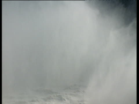 zoom out from mist to niagara falls spilling over cliff edge - niagara falls stock videos and b-roll footage