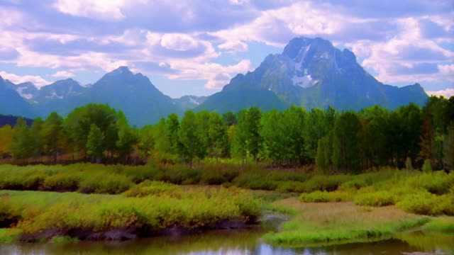Zoom out from Mt. Moran and Grand Teton National Park to wide shot with pond in foreground / Wyoming