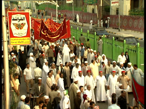 stockvideo's en b-roll-footage met zoom out from muslim men in procession during maulid festival celebrating birth of prophet mohammed cairo - kleding