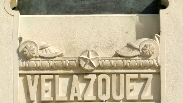 zoom out from name of spanish artist velazquez at base of statue to view of statue and frieze over west entrance to the prado / madrid, spain - fries säulengebälk stock-videos und b-roll-filmmaterial