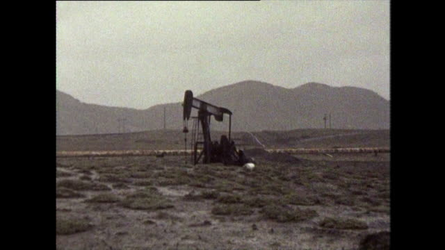 zoom out from oil pumpjack over oil field - oil industry stock videos & royalty-free footage
