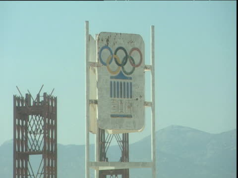 stockvideo's en b-roll-footage met zoom out from olympic sign to olympic stadium for 2004 olympic games blue sky athens - athene griekenland
