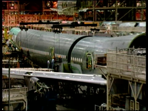 Zoom out from partially constructed large aeroplane at Boeing plant