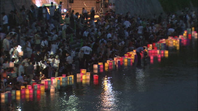 vidéos et rushes de zoom out from people on bank of motoyasu river releasing coloured lanterns in annual ceremony in memory of dead at illuminated hiroshima peace memorial (genbaku dome) - spiritualité