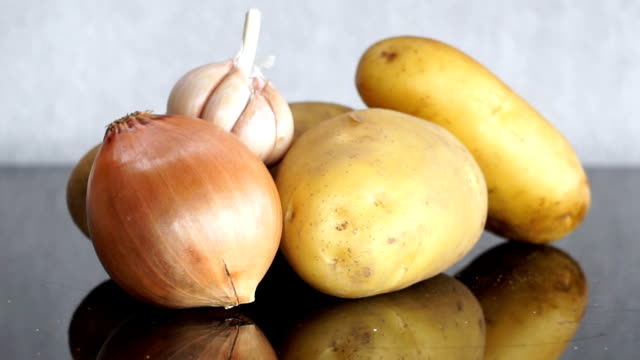 zoom out from potatoes, garlic and onion on table - onion stock videos & royalty-free footage