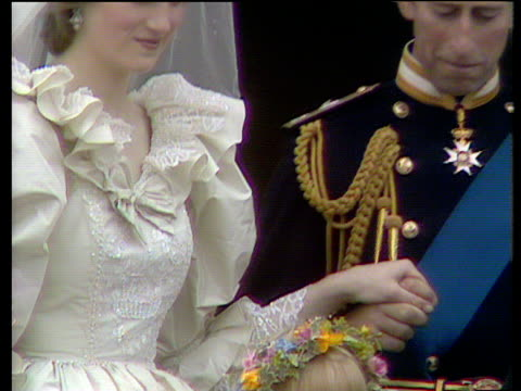 stockvideo's en b-roll-footage met zoom out from prince and princess of wales holding hands on balcony to them smiling and waving as they enter palace royal wedding of prince charles... - prinses