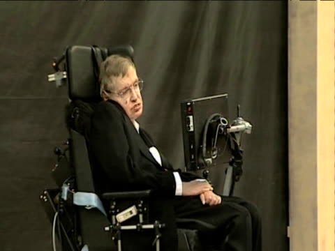 Zoom out from Professor Stephen Hawking attending an unveiling ceremony UK