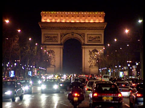Zoom out from road leading to Arc de Triomphe revealing traffic and city lights of Champ Elysees Paris