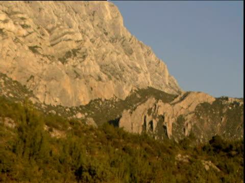 vídeos de stock, filmes e b-roll de zoom out from rocks to st victoire mountain against blue sky aix en provence - aix en provence
