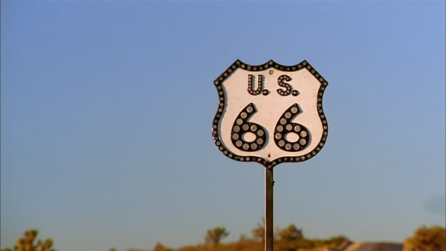 vidéos et rushes de zoom out from route 66 sign to desert highway - route 66
