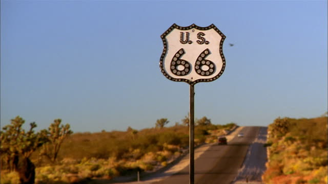 vidéos et rushes de zoom out from route 66 sign to desert highway w/cars driving - route 66